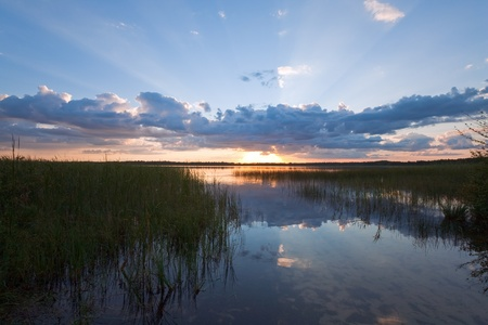 rushy: Summer rushy Lake sunset view with cloud reflections in water surface Stock Photo