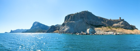 Summer rocky coastline and Genoese fortress (Sudak Town, Crimea, Ukraine). All peoples and cars is unrecognizable. Three shots stitch image. photo