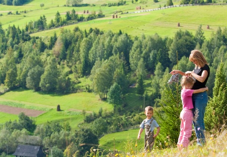 Family resting in a summer mountain walk photo