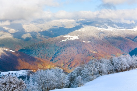 October mountain beech forest edge with first winter snow and last autumn colourful foliage on far mountainside (Carpathian, Ukraine) photo