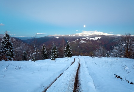 Winter night mountain dirty road, forest with last autumn foliage and Moon on twilight sky (Petros and Goverla Mountain, Carpathian, Ukraine) photo