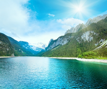 Beautiful summer Alpine  lake Gosausee view and sunshine in sky (Austria)