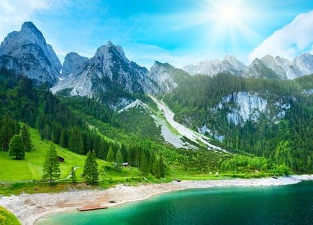 美しい夏のアルプスの山の湖の眺めと空に太陽の光 写真素材