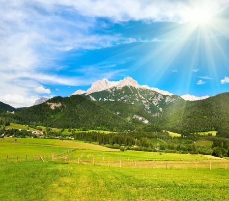 Alps mountain meadow tranquil summer view and sunshine in sky (Austria, Gosau village outskirts) Standard-Bild