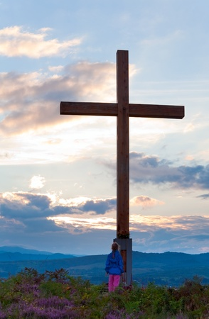 Small girl near wooden cross on summer heather flower hill top and evening country view behind