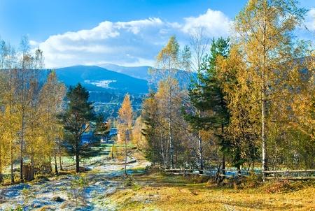 Autumn hoarfrost on mountain village outskirts glade photo