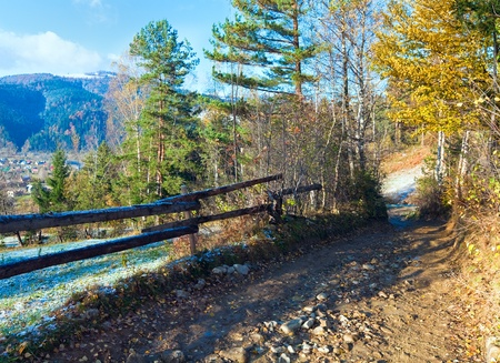 Country dirty road and first autumn hoarfrost on mountain village outskirts photo