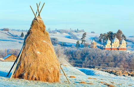 Autumn morning hoarfrost on mountain village outskirts pasture and haystack Stock Photo