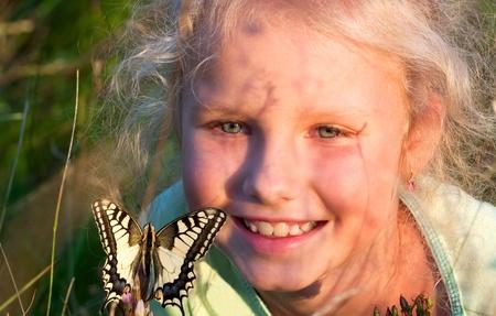 bewonderen: Klein meisje in wilde grassen te bewonderen op geel Swallowtail vlinder