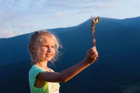 bewonderen: Kleine verbranden Kaukasisch meisje in laatste berg zonsondergang licht te bewonderen op geel Swallowtail vlinder Stockfoto