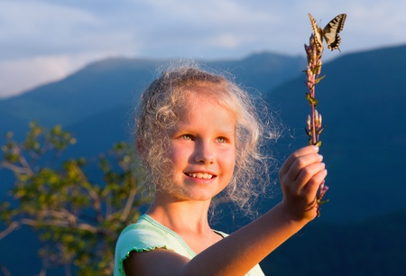 Small sunburnt caucasian girl in last mountain sunset light admire on yellow Swallowtail butterfly