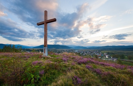 Summer evening country foothills view with heather flowers and wooden cross (Lviv Oblast, Ukraine) .  Stock Photo