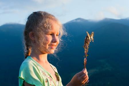 bewonderen: Klein meisje in zonsondergang berg te bewonderen op geel Swallowtail vlinder