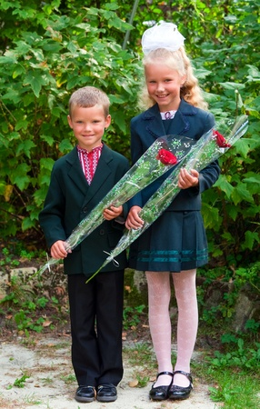 school uniform girl: Outdoor portrait of nice little girl and boy before they first visit to the school