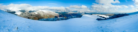 October mountain beech forest edge with first winter snow and last autumn colourful foliage on far mountainside. Four shots stitch image. photo