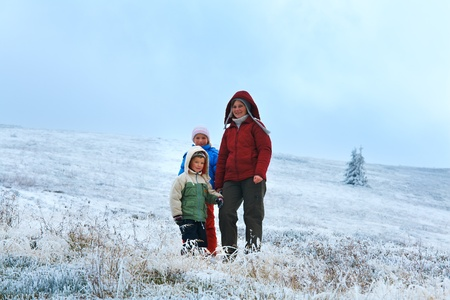 Family (mother with children) on autumn mountain plateau with first winter snow.