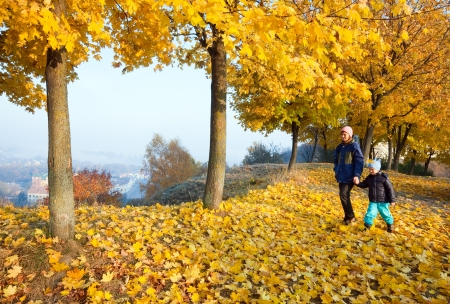 foggy hill: Happy family (mother with small son) walking in golden maple autumn park Stock Photo