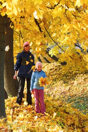 Happy family (mother with daughter) walking in golden maple autumn park photo