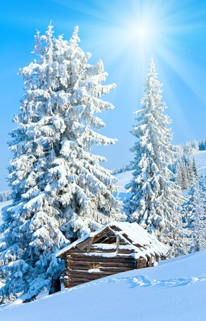 winter calm mountain landscape with shed and sunshine in blue sky (Kukol Mount, Carpathian Mountains, Ukraine) photo