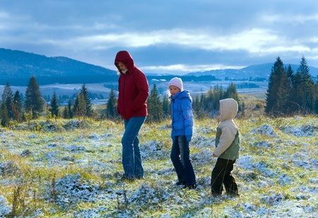 October Carpathian mountain plateau with first winter snow and mother walk with children photo