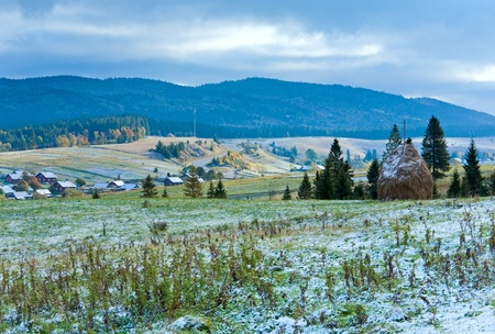 First winter snow on October Carpathian mountain plateau with mountain village and highway far away photo