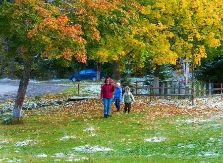 Religion christianity cross near road  and first winter snow on autumn colourful maple foliage (Carpathian, Ukraine) photo
