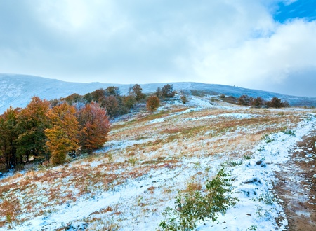 October Carpathian mountain plateau with first winter snow and autumn colorful trees photo