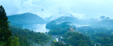 Cloudburst above historic medieval Neuschwanstein Castle in Bavaria (Germany). View from Neuschwanstein Palace.  Five shots composite picture. photo