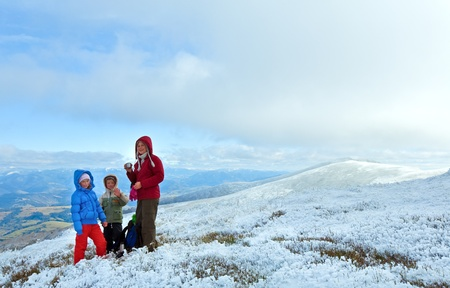 borghava: Family (mother with children) drink hot tea on autumn  mountain plateau with first winter snow