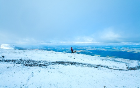 Family (mother with children) drink hot tea on autumn mountain plateau with first winter snow photo