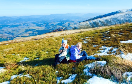 borghava: Children (small boy and girl) rest on autumn  mountain plateau with first winter snow