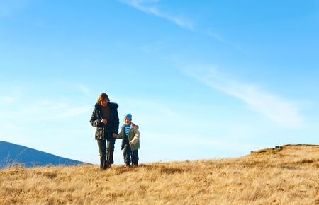 Family (mother with small son) walk on autumn  mountain plateau