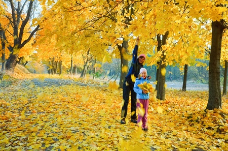 mothering: Happy family (mother with daughter) walking in golden maple autumn park