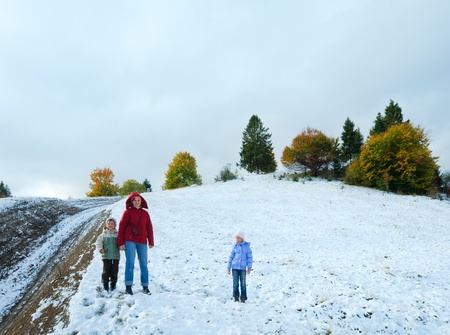 October Carpathian mountain plateau with first winter snow and autumn colorful foliage (and mother with children) photo