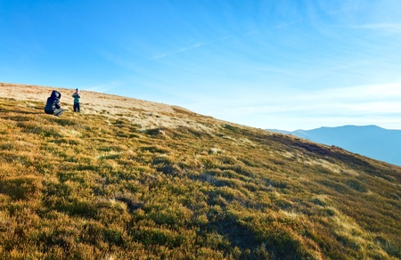 Family (mother with son) walk and make photo on autumn  mountain plateau.