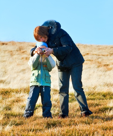Family (mother with son) walk and make photo on autumn  mountain plateau