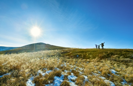 borghava: Family (mother with children) walk on autumn  mountain plateau with first winter snow