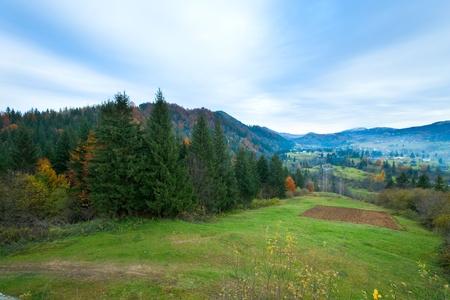 Autumn misty mountain landscape (dull day) with village in valley (Carpathian, Ukraine)