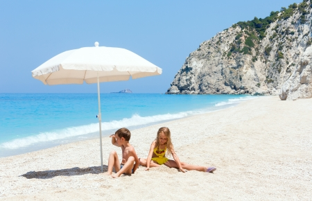 Two children on white beach near azure Ionian sea (Egremni, Lefkada, Greece) photo