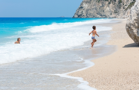 Two children have the water-based recreation on white beach near azure Ionian sea (Egremni, Lefkada, Greece) photo
