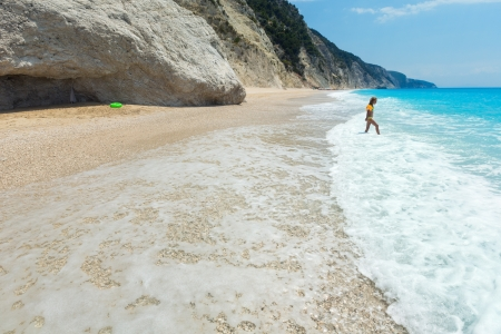 Girl have the water-based recreation on white beach near azure Ionian sea (Egremni, Lefkada, Greece) photo