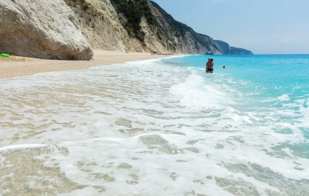Family have the water-based recreation on white beach near azure Ionian sea (Egremni, Lefkada, Greece) photo