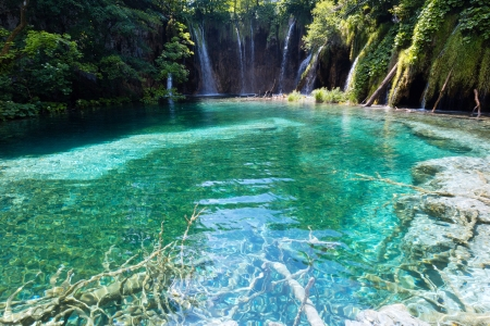 Beautiful lake with clear sea-green water and waterfall behind (Plitvice Lakes National Park, Croatia) photo