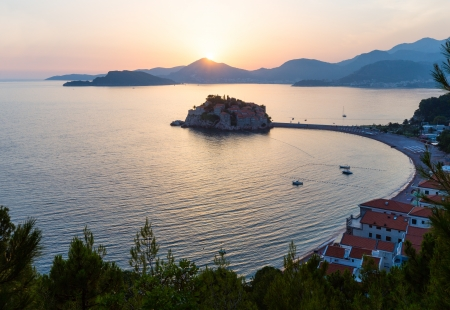 islet: Pink sunset and Sveti Stefan sea islet view from up (Montenegro, 6 kilometres southeast of Budva) Stock Photo