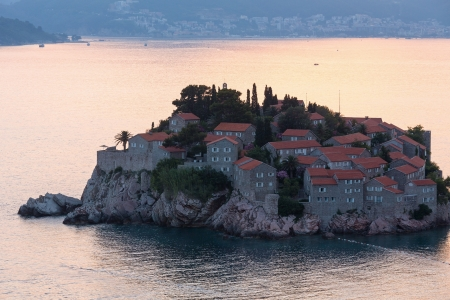 kilometres: Pink sunset and Sveti Stefan sea islet  with town-hotel view from up (Montenegro, 6 kilometres southeast of Budva)