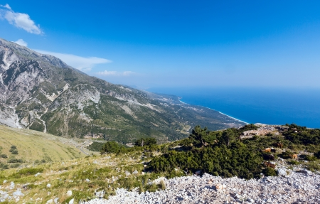 Summer  Llogara pass view  with road, herd of goats on slope and sea water surface (Albania) photo
