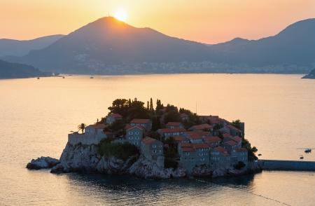 kilometres: Pink sunset and Sveti Stefan sea islet view from up (Montenegro, 6 kilometres southeast of Budva) Editorial
