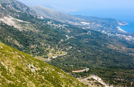 Summer misty  coastline view from  Llogara pass and town on mountainside (Albania) photo