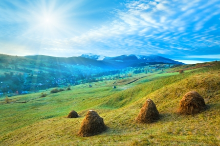 Misty morning in autumn Carpathian mountain, Ukraine (Goverla and Petros Mount in far) with sunshine and haystack photo