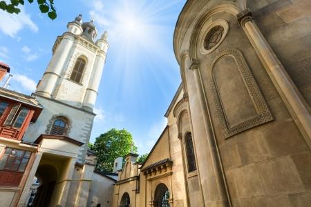 Ancient armenian church in Lviv City (Ukraine) and sunsshine in blue summer sky photo